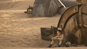 Rey is sitting against the foot of a fallen AT-AT, which is awesomely, her home.