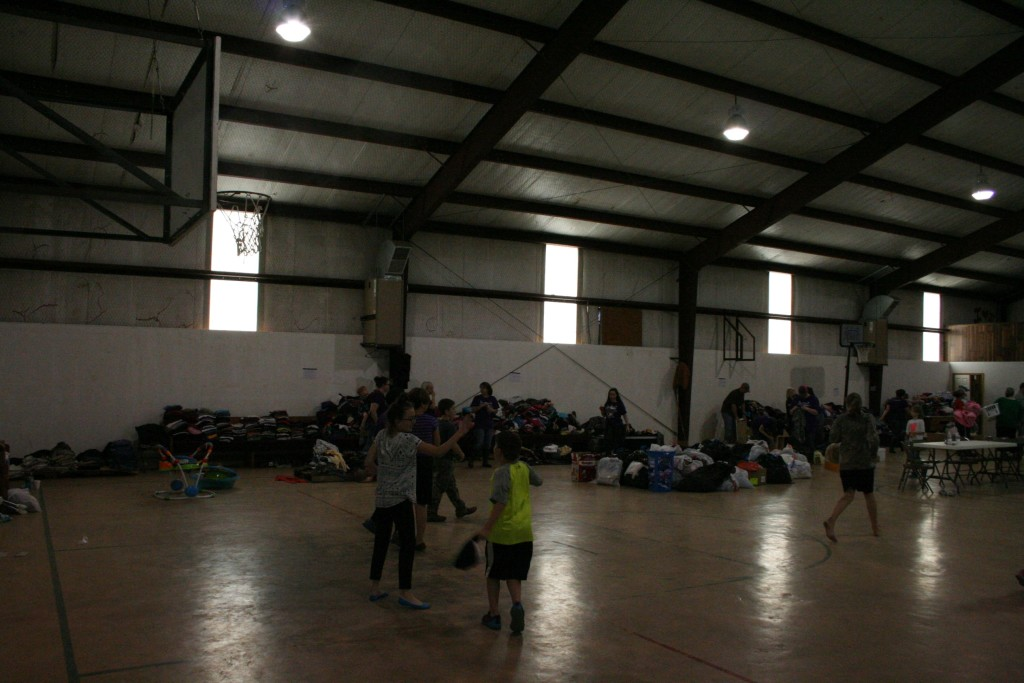 We visited the youth center at Evans. Some kids were playing basketball and just trying to have some fun. In the background are clothes galore and people were looking through them. This shows that the community was working to help each other.